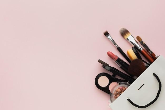 Moldura de vista superior com produtos de maquiagem em um saco Foto gratuita
