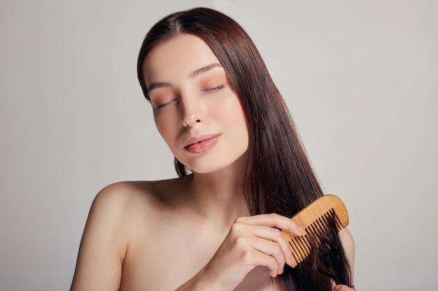 Moldura do meio, uma mulher com humor brincalhão penteia o cabelo com um pente marrom claro com os olhos fechados Foto Premium