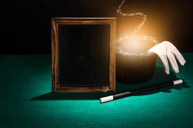 Moldura em branco de madeira; varinha mágica e brilhante cartola com luvas brancas sobre fundo verde Foto gratuita