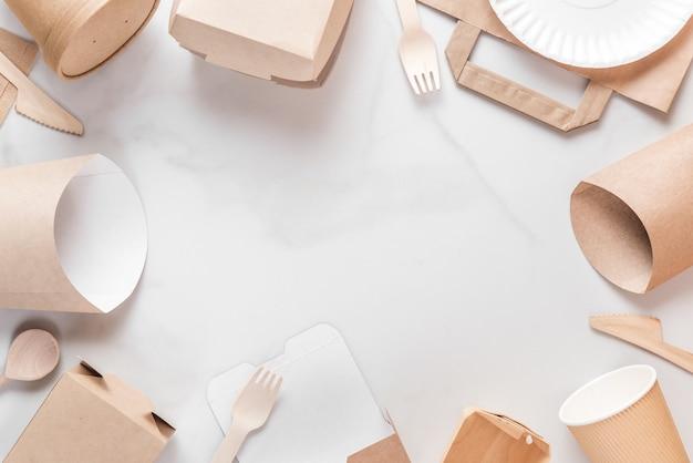 Moldura feita de utensílios de mesa descartáveis ecológicos. copos de papel, pratos, sacolas, recipientes de fast food e talheres de madeira de bambu Foto Premium