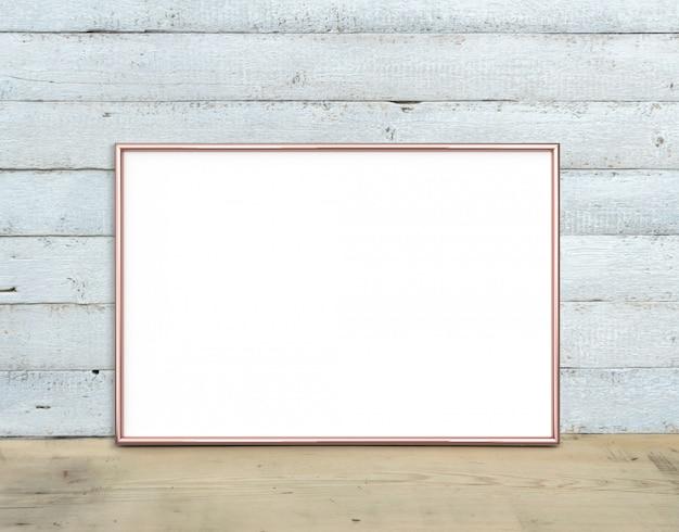 Moldura horizontal em ouro rosa a4 fica em uma mesa de madeira Foto Premium
