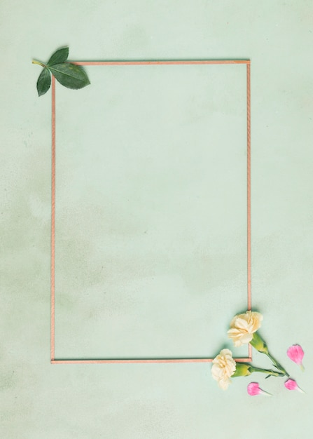 Moldura minimalista com cravo flores e folhas no fundo azul Foto gratuita