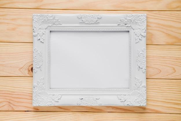 Moldura ornamental branca com fundo de madeira Foto gratuita