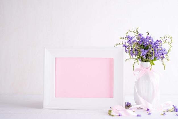 Moldura para retrato branca com a flor roxa bonita no vaso na tabela de madeira branca. Foto Premium