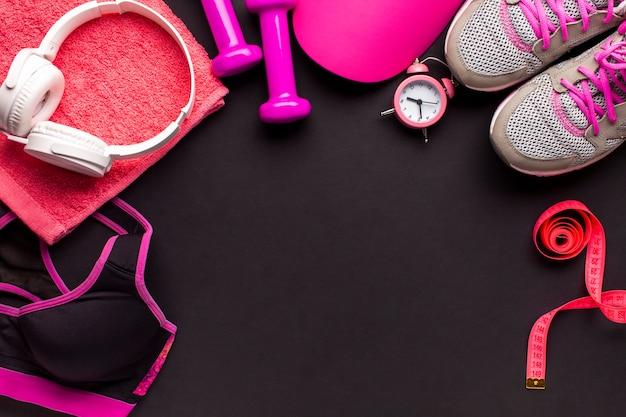 Moldura plana com itens-de-rosa e fones de ouvido brancos Foto gratuita