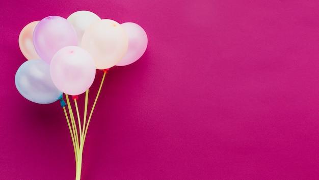 Moldura plana leiga com balões e fundo rosa Foto gratuita