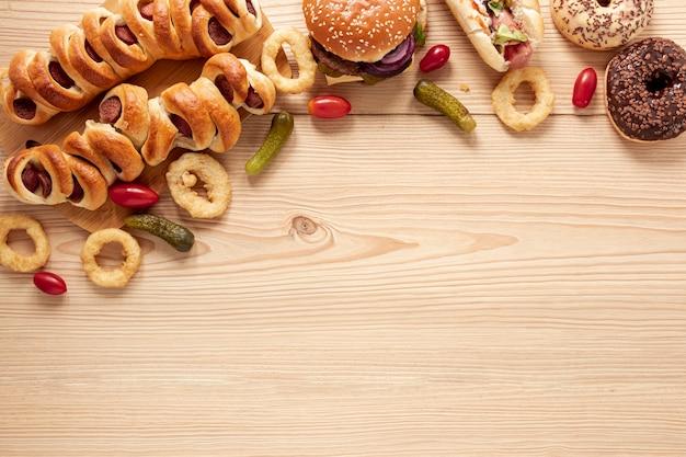 Moldura plana leiga com comida deliciosa e fundo de madeira Foto gratuita