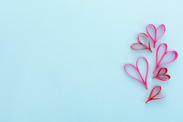Moldura plana leiga com formas de coração e fundo azul Foto gratuita