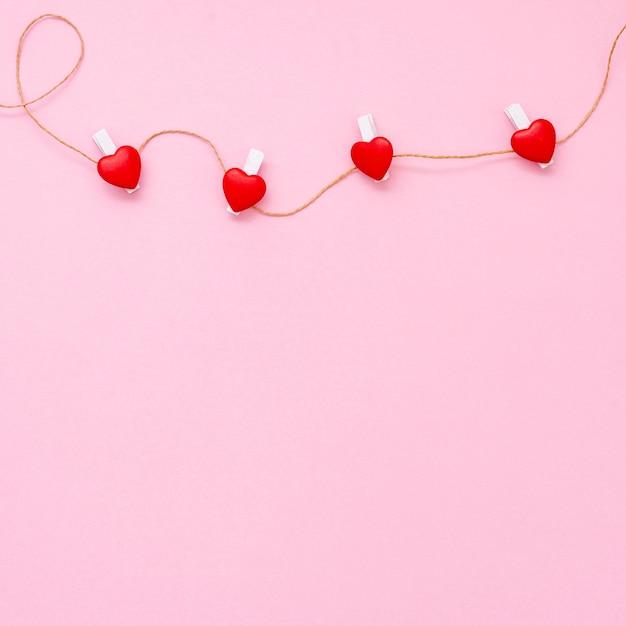 Moldura plana leiga com pequenos corações e fundo rosa Foto gratuita