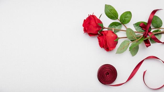 Moldura plana leiga com rosas e fita vermelha Foto gratuita