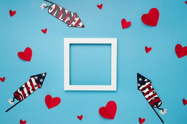 Moldura quadrada branca sobre fundo azul com corações de papel e fogos de artifício para o dia da independência Foto gratuita
