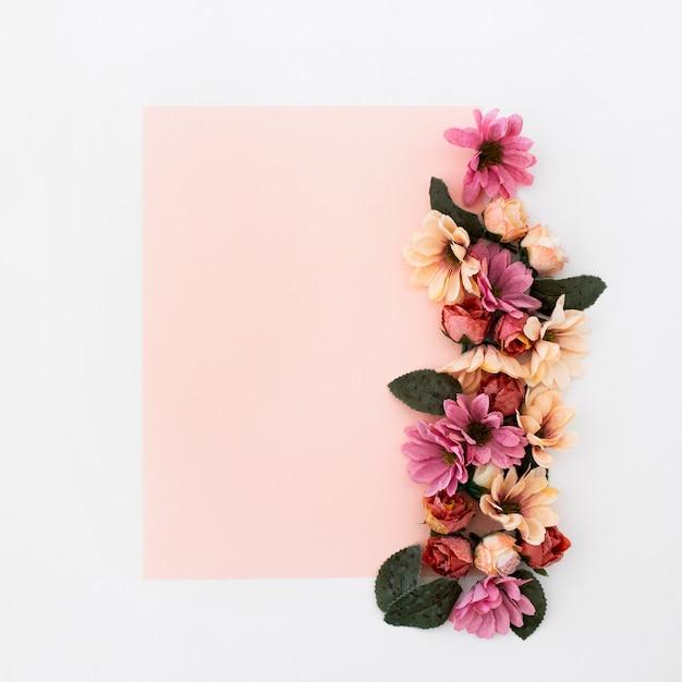 Moldura rosa com flores ao redor Foto gratuita