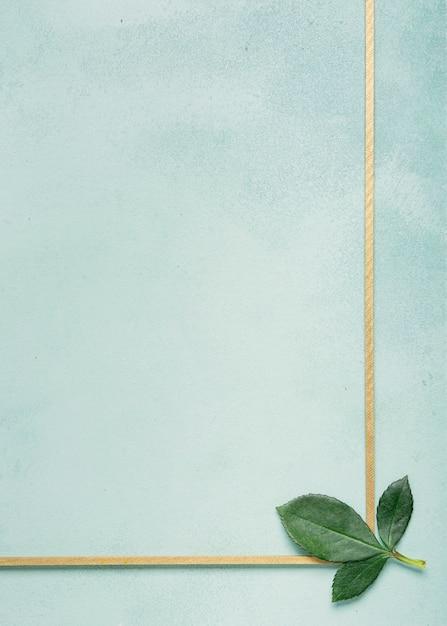 Moldura simplista com cravo deixa na superfície azul Foto gratuita