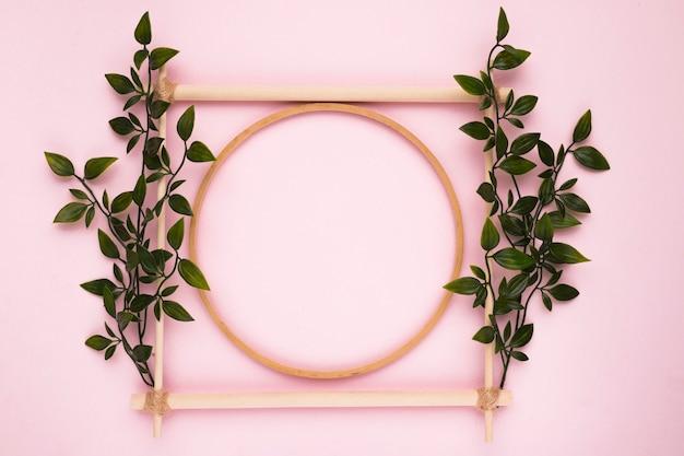 Moldura vazia de madeira decorativa com folhas na parede rosa Foto gratuita