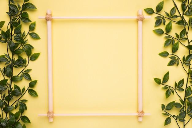 Moldura vazia de madeira em papel amarelo com folhas artificiais verdes Foto gratuita