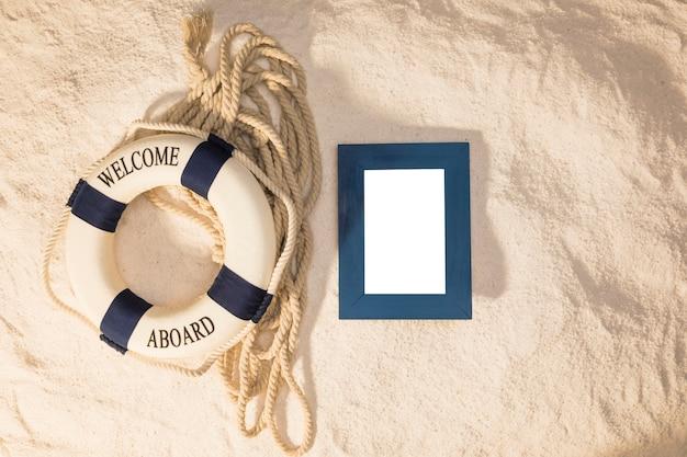 Moldura vazia e lifebuoy marinho na areia Foto gratuita