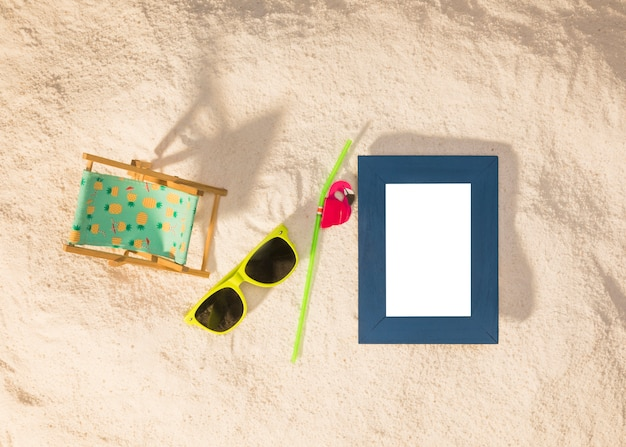 Moldura vertical azul e óculos de sol na praia Foto gratuita