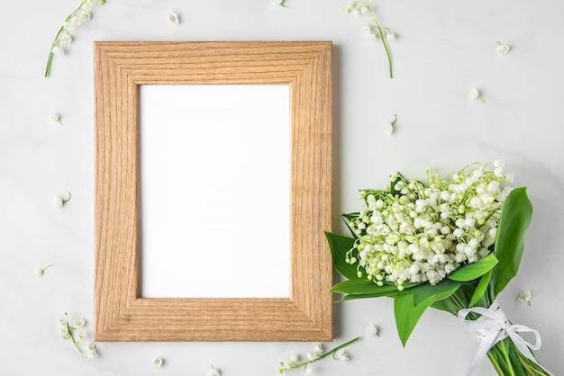 Molduras para fotos em branco com buquê de flores de lírio do vale em branco. configuração plana. vista do topo Foto Premium