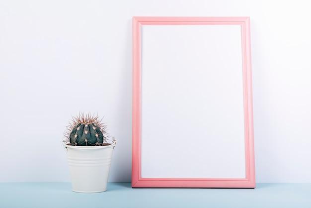 Molduras para fotos em branco com pequena planta suculenta em vaso na mesa azul Foto gratuita