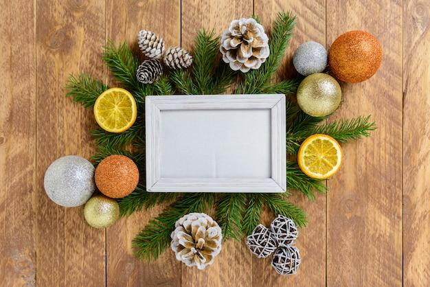 Molduras para fotos entre a decoração de natal, com bolas coloridas e pinhas em uma mesa de madeira marrom. vista superior, moldura para copiar o espaço. Foto Premium
