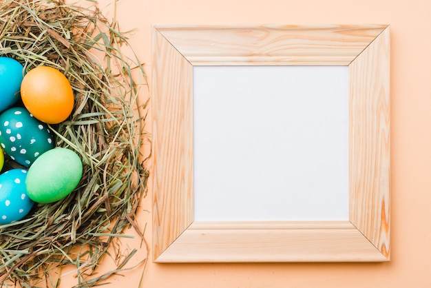 Molduras para fotos perto de conjunto de ovos de páscoa brilhantes no ninho Foto gratuita