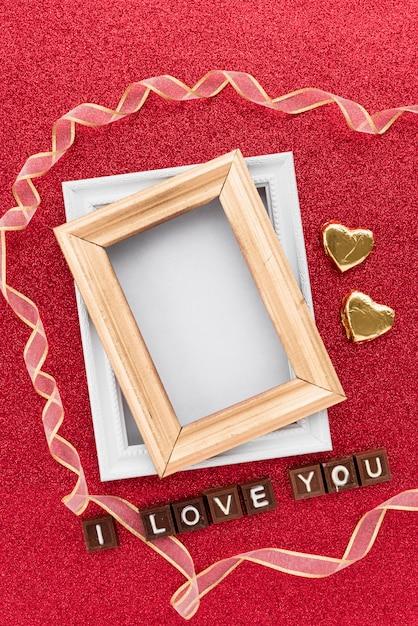 Molduras perto corações ornamento, fita e eu te amo inscrição Foto gratuita