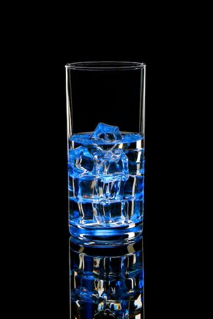 Molhe com gelo em um copo com um brilho azul. cocktail refrescante em um preto Foto Premium