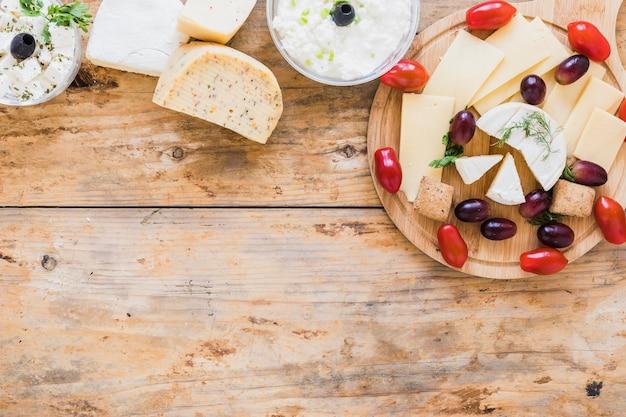 Molho de queijo e blocos com uvas e tomates na mesa de madeira Foto gratuita