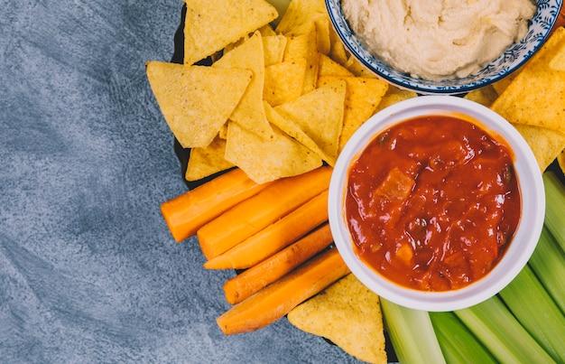 Molho de salsa em tigela sobre cenoura; talo de aipo e tortilla chips em placa Foto gratuita