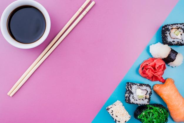 Molho de soja e sushi de vista superior rola na mesa Foto gratuita