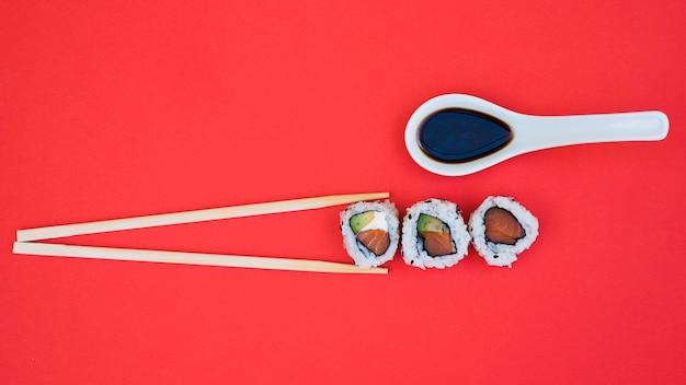 Molho de soja na colher com pauzinhos e sushi no fundo vermelho Foto gratuita