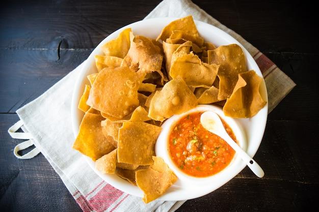 Molho vermelho picante com um prato de tortilla chips Foto Premium