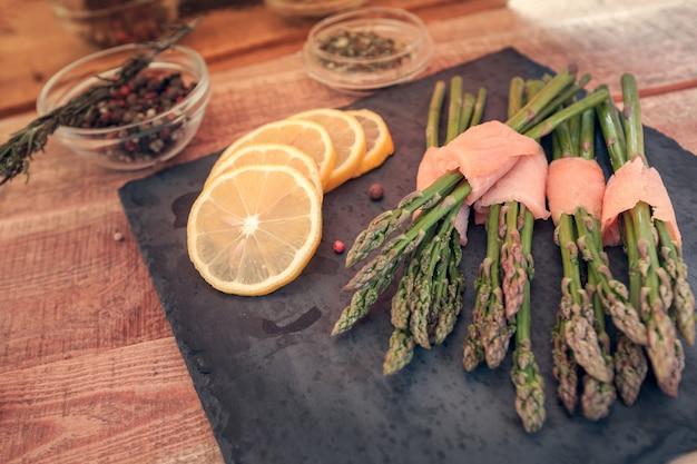 Molhos de espargos envoltos em salmão com especiarias Foto Premium