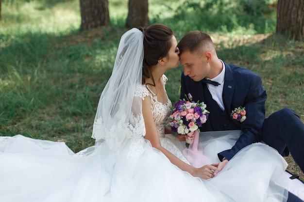 Momento de casamento romântico. casal jovem feliz casamento abraçando ao ar livre no parque verde. noiva emocional em vestido branco e noivo de terno na caminhada na primavera. Foto Premium