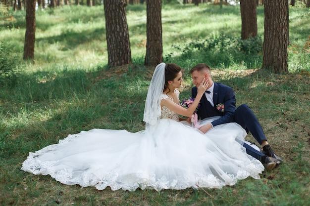 Momento de casamento romântico. casal jovem feliz casamento abraçando ao ar livre no parque verde. retrato bonito dos recém-casados ao ar livre. Foto Premium