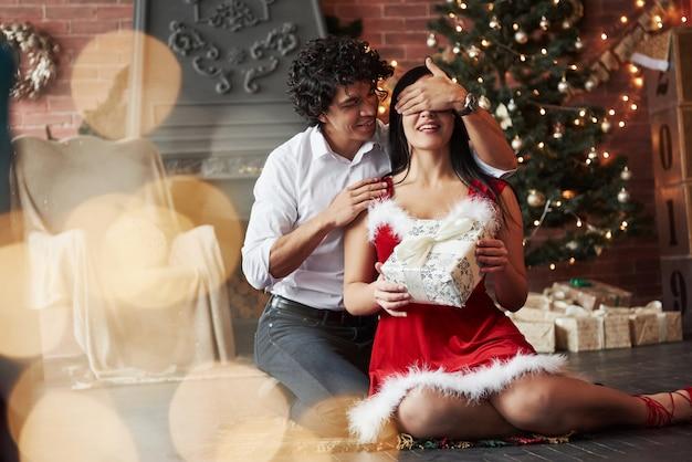 Momento lindo. homem fazendo surpresa para a namorada. dá presente de ano novo. jovem casal senta-se no chão da sala de quarto decorado de férias Foto Premium