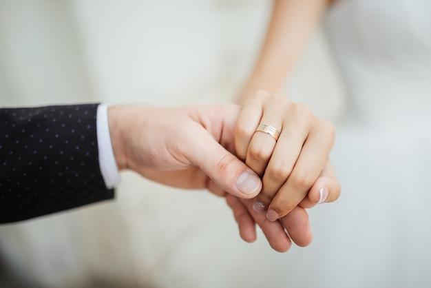 Momentos de casamento. recém casar as mãos do casal com anéis de casamento Foto gratuita