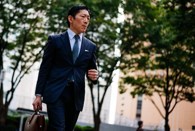 Momentos de homem de negócios sênior nas ruas de tóquio Foto Premium