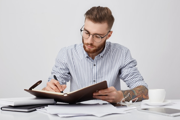 Momentos de trabalho. homem tatuado sério e concentrado, usando camisa formal e óculos redondos Foto gratuita