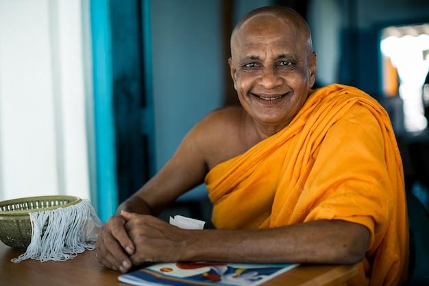 Monge budista asiático idoso sorrindo para a câmera no mosteiro budista no rio Foto gratuita