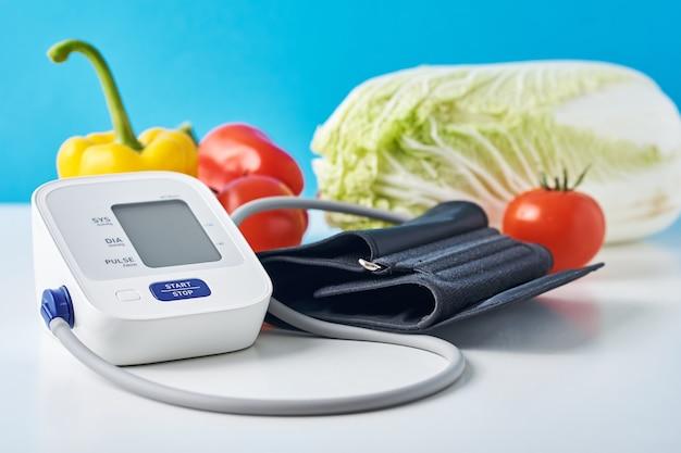 Monitor da pressão sanguínea de digitas e legumes frescos na tabela contra o azul. Foto Premium