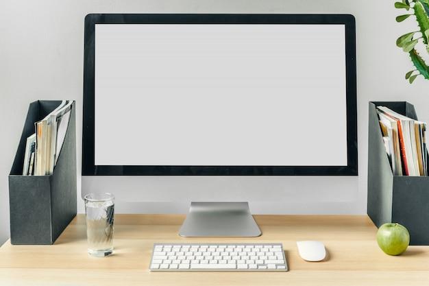 Monitor de computador com tela branca de maquete na mesa de escritório com suprimentos Foto Premium