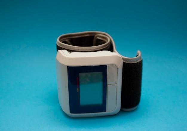 Monitor de pressão arterial digital automático de pulso sobre fundo azul. Foto Premium