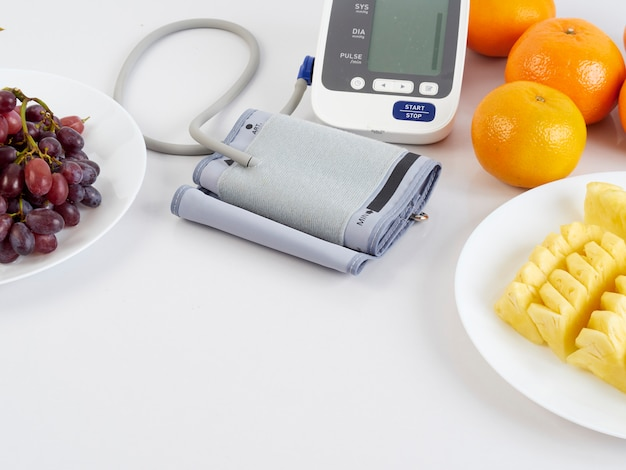Monitor de pressão arterial e frutas Foto Premium