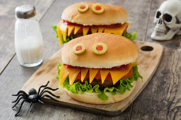 Monstros de hambúrguer de halloween na mesa de madeira Foto Premium