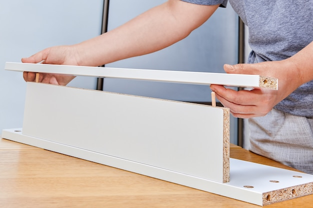 Montagem de móveis, instalador montando dois aglomerados com ferragens conectadas a móveis, como pino-guia de madeira. Foto Premium