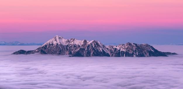 Montanha coberta de neve, cercada pelo mar de nuvens Foto gratuita