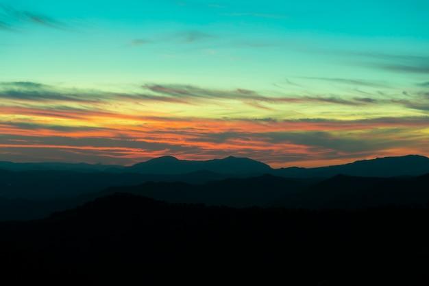 Montanha panorâmica e fundo do pôr do sol do céu dramático Foto gratuita