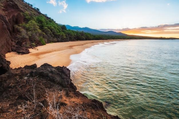 Montanha verde e marrom ao lado do corpo de água Foto gratuita