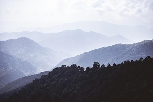 Montanhas arborizadas em um deus sob um céu nublado Foto gratuita